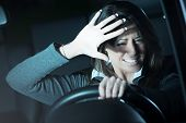 stock photo of terrifying  - Young terrified woman driving and having a car accident at night.