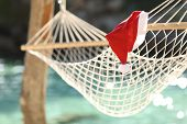 stock photo of beach holiday  - Hammock in a tropical beach on christmas holidays with the clean water of the sea in the background - JPG