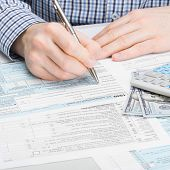 picture of cpa  - Male filling out 1040 USA Tax Form - studio shot