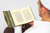 picture of islamic religious holy book  - Photo of the Young man reading the Holy Koran - JPG