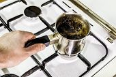 image of brew  - Black coffee is brewed and boils in a pot on the stove - JPG