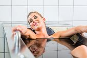 foto of mud  - Senior woman enjoying mud bath alternative therapy - JPG