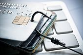 stock photo of theft  - a fish hook on piles of credit cards over computer keyboards  - JPG