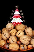 stock photo of walnut-tree  - Wooden bowl full of Walnuts and Hazelnuts with a pretty tin Christmas tree to the rear against a black background - JPG