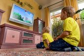 image of watch  - children sit in front of a tv and watch a children - JPG
