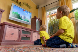 stock photo of tv sets  - children sit in front of a tv and watch a children - JPG