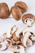 picture of agaricus  - Diced and whole agaricus brown button mushrooms also known as portobello as they increase in size ready to be used as a savory cooking ingredient or in vegetarian and vegan cuisine