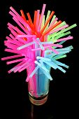 stock photo of water shortage  - long drink glass with some water and many colored plastic straws symbolizing water global shortage - JPG