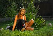 picture of stray dog  - A young beautiful woman with blonde hair is holding lovingly a stray dog in her arms in a backyard garden with green grass - JPG