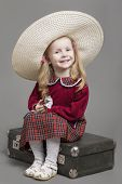 foto of outdated  - Happy And Smiling Caucasian Child Posing in Big Round Sombrero Hat and Sitting on Outdated Suitcase - JPG
