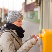 stock photo of postbox  - Young woman posting a letter - JPG