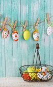 stock photo of bucket  - Colorful easter eggs in bucket and on clothes line on wooden background - JPG