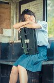 image of daydreaming  - Cute Thai schoolgirl is daydreaming in an old bus stop - JPG