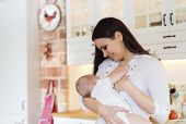 foto of breastfeeding  - Mother breastfeeding her little baby girl in her arms - JPG