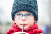 stock photo of hot water  - Cute little girl drinking water/juice/ hot chocolate through a straw outdoors - very shallow deep of field ** Note: Visible grain at 100%, best at smaller sizes - JPG