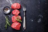 image of red meat  - Raw fresh marbled meat Steak seasonings and meat fork on dark marble background - JPG