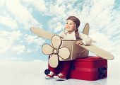 stock photo of clouds sky  - Little Child Playing Airplane Pilot Kid Traveler Flying in Aviator Helmet on Travel Suitcase Vacation Trip Concept over Blue Sky Clouds - JPG