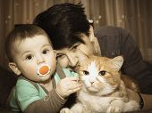 image of baby cat  - Caucasian family mother and baby playing with red cat - JPG