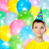 pic of young boy  - Portrait of happy boy with birthday cap on abstract colorful balloons background - JPG