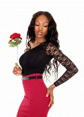 stock photo of woman red blouse  - A lovely slim African American woman in a red skirt and black blouse standing isolated for white background holding a red rose - JPG
