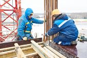 picture of millwright  - construction workers installing framework for concrete at building area  - JPG