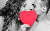 stock photo of nack  - Attractive young couple kissing behind red heart against black  - JPG