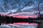 foto of ponds  - The setting sun paints the sky with vivid and dramatic colors that is reflected on a small Indiana pond - JPG