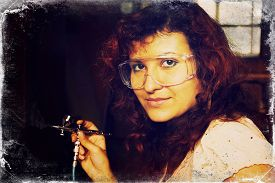 stock photo of airbrush  - A young woman painting with airbrush equipment and airbrush gun - JPG
