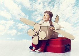 stock photo of blue  - Little Child Playing Airplane Pilot Kid Traveler Flying in Aviator Helmet on Travel Suitcase Vacation Trip Concept over Blue Sky Clouds - JPG