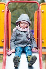 picture of chute  - Serious girl girl on children chute ready to slide in wintertime - JPG