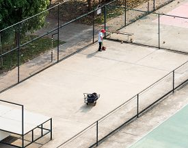 image of sweeper  - Young sweeper is cleaning the sport field - JPG