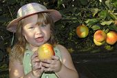 pic of country girl  - a young girl eating an apple in the sun - JPG
