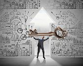 pic of keyhole  - Young businessman and keyhole at background lifting big key above head - JPG