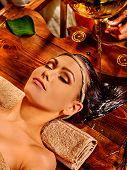 stock photo of panchakarma  - Young woman lying on back having oil Ayurveda spa treatment - JPG