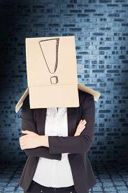 image of lifting-off  - Businesswoman lifting box off head against dark grey room - JPG