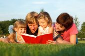 pic of girl reading book  - Sweet family reading a book on the green grass - JPG