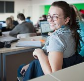 image of students classroom  - young pretty female college student sitting in a classroom full of students during class - JPG