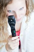 pretty female doctor/optometrist checking your eyes with an ophthalmoscope (shallow DOF - selective