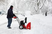 Man using a snow blower to clear out his driveway