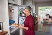 Senior woman removing eggs tray from refrigerator to prepere a pie. Mature woman holding eggs tray w poster
