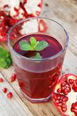 Glass Of Pomegranate Juice And Pomegranate Fruit On Wooden Background poster