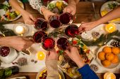 holidays and celebration concept - close up of friends having christmas dinner at home, drinking red poster