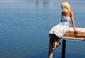 Постер, плакат: Девочка сидит на Пирс на берегу реки естественного солнечного света