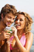 Постер, плакат: Молодая красивая пара на побережье пить коктейли