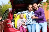 Young Family Having Rest Near Car Trunk Loaded With Suitcase Outdoors poster