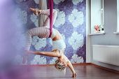 Young Woman Doing Aerial Yoga Practice In Purple Hammock In Fitness Club. poster