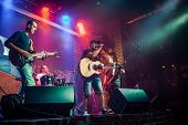 Band performs on stage, rock music concert in a nightclub. Authentic shooting with high iso in chall poster