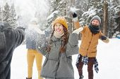 Happy young friends in winter coats having snowball fight in forest: excited girl standing in center poster