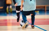 Young Futsal Players And Soccer Ball With Motion Blur. Indoor Futsal Soccer Players In Motion Playin poster