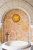 stock photo of christening  - Baptismal area inside Catholic church with the Holy Spirit and water basin - JPG